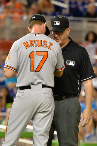 May 23, 2015; Miami, FL, USA; MLB umpire Paul Emmel (right) examines Baltimore Orioles relief pitcher Brian Matusz (17) arms for foreign substance during the 12th inning against the Miami Marlins  ...