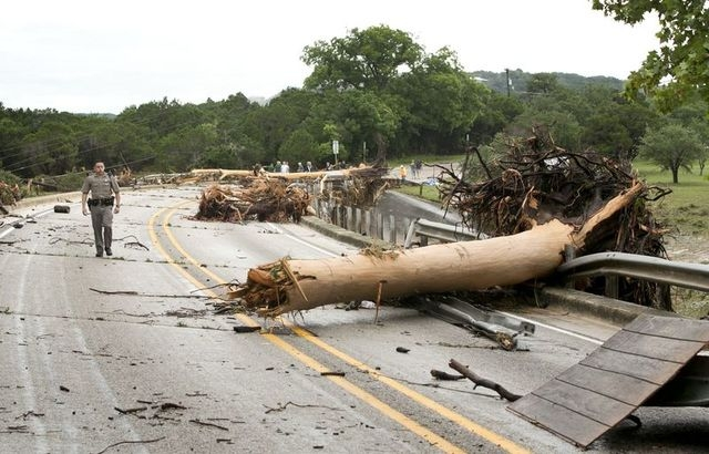 Department of Public Safety Trooper Marcus Gonzales walks on the Highway 12 bridge over the Blanco River which was blocked by large trees after flooding in Wimberly, Texas, United States May 24, 2 ...