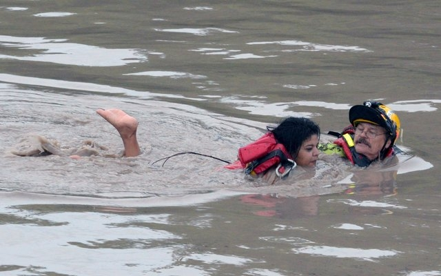 San Marcos Firefighter Jay Horton (R) rescues a woman from in flood waters in San Marcos, Texas May 24, 2015. Texas Governor Greg Abbott on Monday likened the ferocity of flash flooding that kille ...