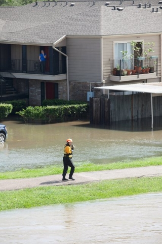 An emergency personnel scans the flood waters of Brays Bayou in Houston, Texas May 26, 2015. Torrential rains have killed at least eight people in Texas and Oklahoma, including two in Houston wher ...