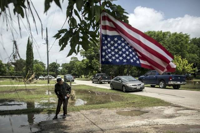 An American flag, a remnant of Memorial Day holiday one day earlier, waves despite being caught in a tree, while Martin Bali, a resident of Austin, Texas, cleans his shoes after visiting a friend  ...