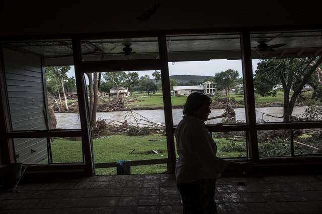 Gay Sullivan surveys the flood damage done to her living room in Wimberley, Texas May 26, 2015. Torrential rains have killed at least 10 people in Texas and Oklahoma, including three in Houston wh ...