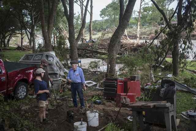 Volunteers from Austin, Texas take a break from cleaning and speak with Michael J. Sullivan (R), whose home was decimated by the Memorial Day weekend floods in Wimberley, Texas May 26, 2015. Torre ...