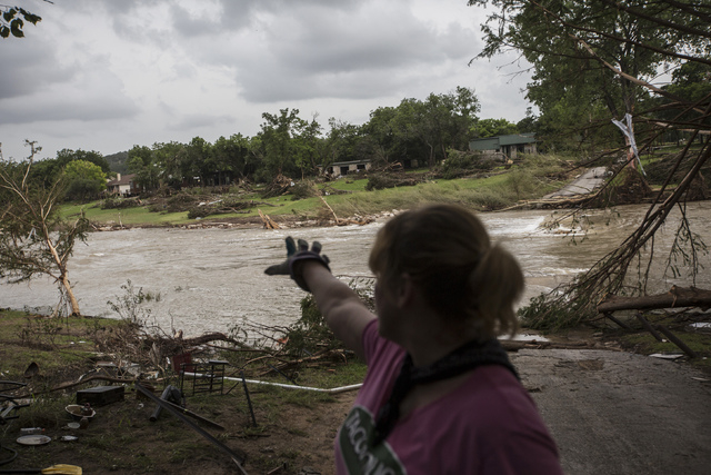 Amy Gilmour describes how the Blanco River crested at a record 43 feet during the Memorial Day weekend floods while helping pick up debris from the backyards of flood damaged homes in Wimberley, T ...