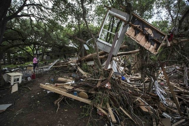 Amy Gilmour, a volunteer from San Antonio, Texas, walks past a pile of debris, which included parts of destroyed homes, that amassed when the Blanco River flooded during the Memorial Day weekend r ...