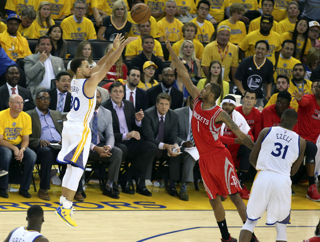 May 27, 2015; Oakland, CA, USA; Golden State Warriors guard Stephen Curry (30) shoots over Houston Rockets forward Trevor Ariza (1) during the second half in game five of the Western Conference Fi ...