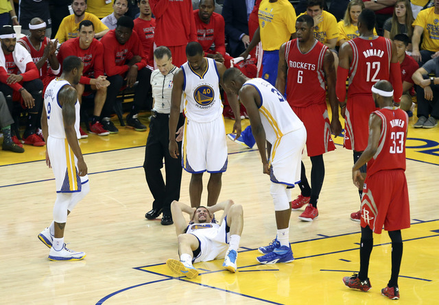 May 27, 2015; Oakland, CA, USA; Golden State Warriors guard Klay Thompson (11) lays injured during the fourth quarter against the Houston Rockets in game five of the Western Conference Finals of t ...