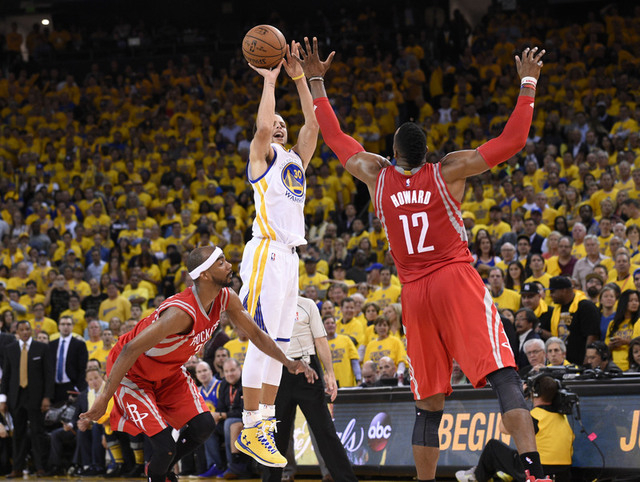 May 27, 2015; Oakland, CA, USA; Golden State Warriors guard Stephen Curry (30) shoots over Houston Rockets center Dwight Howard (12) during the fourth quarter in game five of the Western Conferenc ...