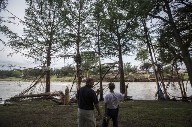 Burns Cleland (L) and Robert Wells (R) survey the flood damage done to the area surrounding the Blanco River in Wimberley, Texas May 26, 2015. (REUTERS/Tamir Kalifa)