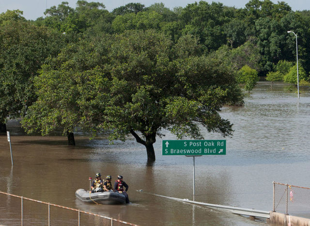 Rescue personnel search the floodwaters along Brays Bayou in southwest Houston, Texas May 26, 2015. (REUTERS/Daniel Kramer)