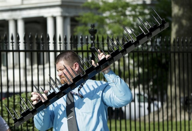 A government contractor carries away an insert of metal spikes that will be placed in  between the original fencing (rear) at the White House in Washington May 28, 2015. The black iron fence surro ...