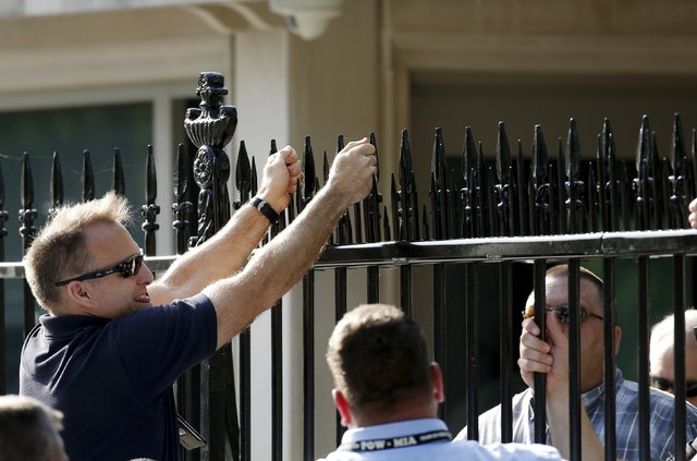 United States Secret Service personnel and government contractors begin work on the White House perimeter fence at the White House in Washington May 28, 2015. The black iron fence surrounding the  ...