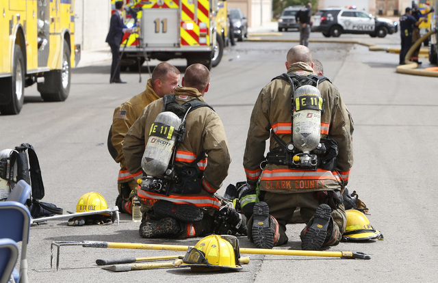 Clark County firefighters take a break after battling an apartment complex fire on Haves St. near Interstate 15 and Pebble Road on Friday, May 8, 2015. At least 10 of 16 units in an apartment comp ...