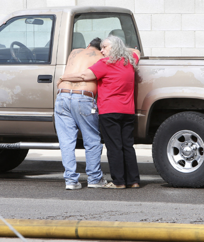 An unidentified resident, right, whose home was destroyed by an apartment complex fire, comforts a man on Haves St. near Interstate 15 and Pebble Road on Friday, May 8, 2015. At least 10 of 16 uni ...