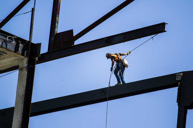 An ironworker guides a beam into place at  the MGM Resorts International-AEG arena construction site behind New York-New York casino-hotel onThursday, April 23, 2015. The $375 million arena is sch ...