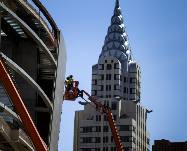 A replica of the Chrysler Tower at New York-New York casino-hotel is seen while work continues at the MGM Resorts International-AEG arena construction site behind  Thursday, April 23, 2015. (Jeff  ...
