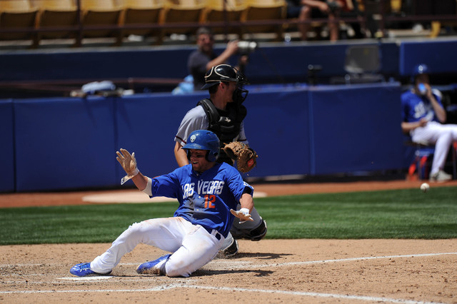 Las Vegas 51s base runner Danny Muno scores a run as Sacramento River Cats catcher Ben Turner fields the late throw in the seventh inning of their Triple-A minor league baseball game at Cashman Fi ...