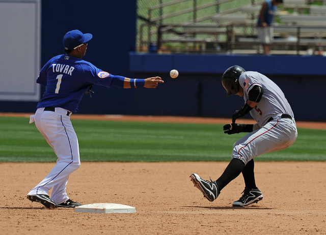 Sacramento River Cats base runner Ronny Cedeno (5) is nearly hit in the head with the baseball while breaking up a double play attempt by Las Vegas 51s shortstop Wilfredo Tovar (1) in the eighth i ...