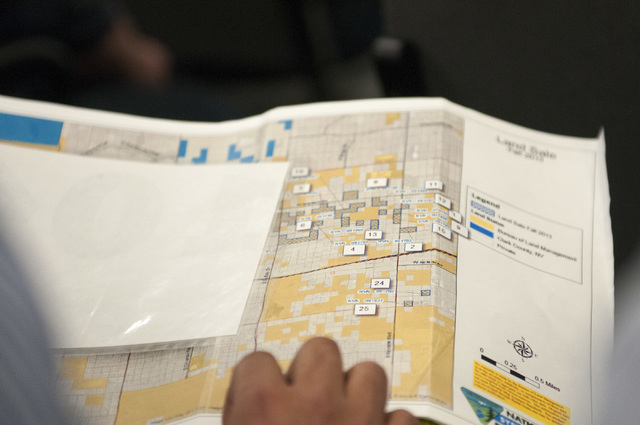 Manny Pattni, vice president at Lewis Operating Corp., looks at a map with available properties during a 28-parcel land sale auction at the Bureau of Land Management in Las Vegas, Jan. 16, 2014. S ...