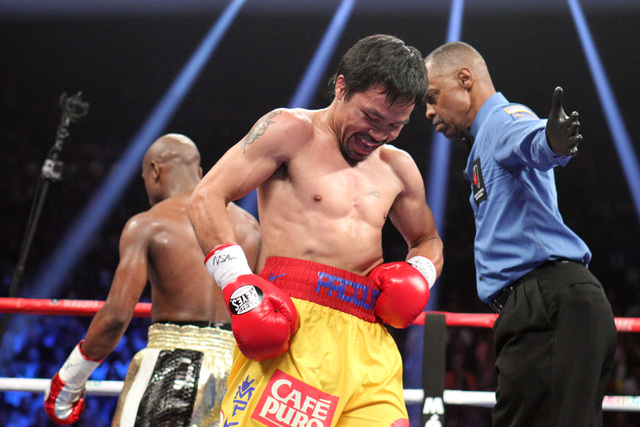 Manny Pacquiao and Floyd Mayweather Jr. head to their corners between rounds of their welterweight unification boxing match at the MGM Grand Garden Arena in Las Vegas on Saturday, May 2, 2015. (Sa ...
