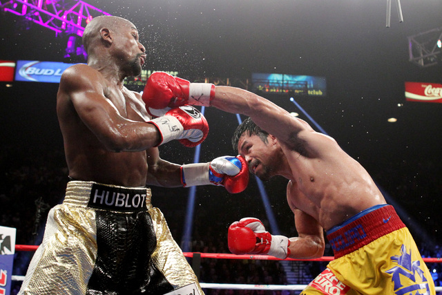 Manny Pacquiao hits Floyd Mayweather Jr. with a left during their welterweight unification boxing match at the MGM Grand Garden Arena in Las Vegas on Saturday, May 2, 2015. (Sam Morris/Las Vegas R ...