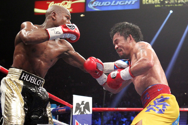 Floyd Mayweather Jr. hits Manny Pacquiao with a left during their welterweight unification boxing match at the MGM Grand Garden Arena in Las Vegas on Saturday, May 2, 2015. (Sam Morris/Las Vegas R ...