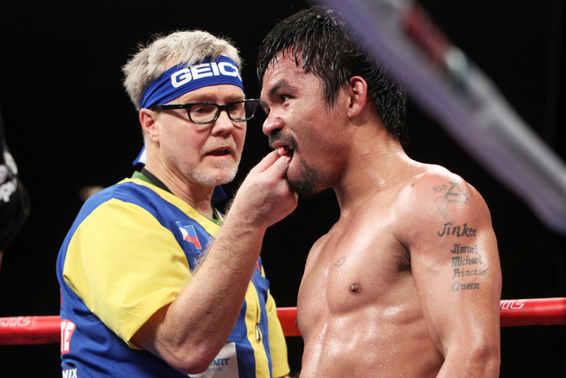 Trainer Freddy Roach removes Manny Pacquiao's mouth guard between round of his welterweight unification boxing match against Floyd Mayweather Jr. at the MGM Grand Garden Arena in Las Vegas on Satu ...
