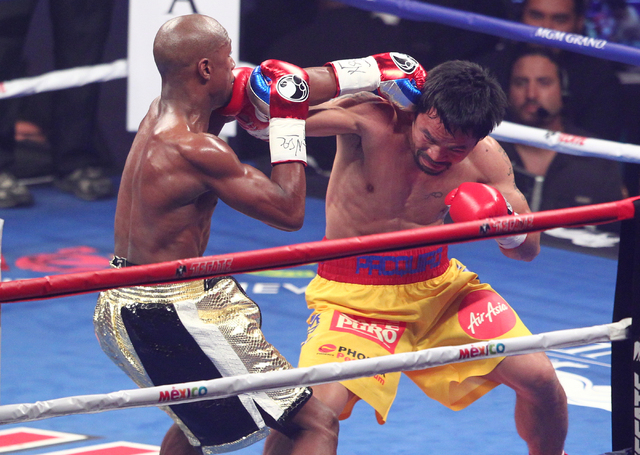 Floyd Mayweather Jr., left, trades punches with Manny Pacquiao in their welterweight unification boxing match at the MGM Grand Garden Arena in Las Vegas on Saturday, May 2, 2015. (Chase Stevens/La ...