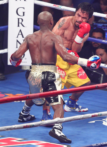 Floyd Mayweather Jr., left, looks to throw a punch at Manny Pacquiao in their welterweight unification boxing match at the MGM Grand Garden Arena in Las Vegas on Saturday, May 2, 2015. (Chase Stev ...