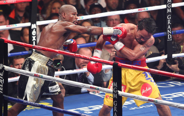 Floyd Mayweather Jr., left, throws a punch at Manny Pacquiao in their welterweight unification boxing match at the MGM Grand Garden Arena in Las Vegas on Saturday, May 2, 2015. (Chase Stevens/Las  ...