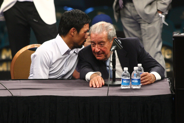 Manny Pacquiao, left, talks with promoter Bob Arum following Pacquiao's defeat by Floyd Mayweather Jr. after their welterweight unification boxing match at the MGM Grand Garden Arena in Las Vegas  ...