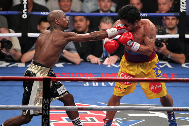 Floyd Mayweather Jr., left, lands a blow to Manny Pacquiao in the sixth round of their welterweight unification boxing match at the MGM Grand Garden Arena in Las Vegas on Saturday, May 2, 2015. (E ...