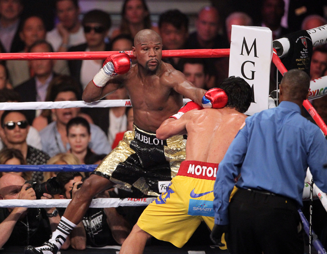 Floyd Mayweather Jr., left, lands a glove on Manny Pacquiao in the sixth round of their welterweight unification boxing match at the MGM Grand Garden Arena in Las Vegas on Saturday, May 2, 2015. ( ...