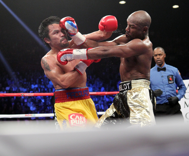 Floyd Mayweather Jr., left, and Manny Pacquiao mix it up in the eighth round of their welterweight unification boxing match at the MGM Grand Garden Arena in Las Vegas on Saturday, May 2, 2015. (Sa ...