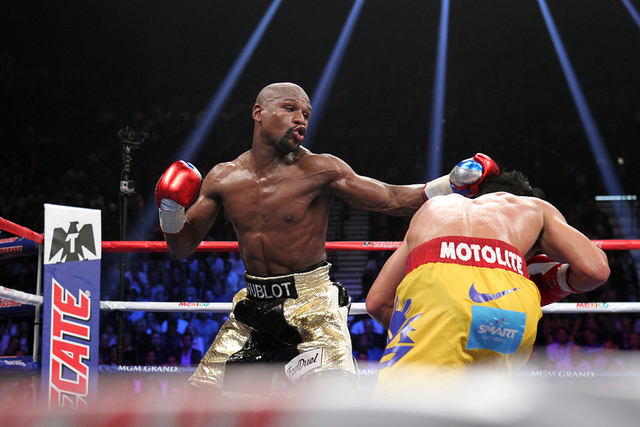 Floyd Mayweather Jr. lands a left to Manny Pacquiao in the ninth round of their welterweight unification boxing match at the MGM Grand Garden Arena in Las Vegas on Saturday, May 2, 2015. (Sam Morr ...