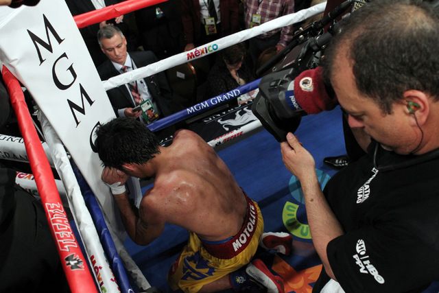 Manny Pacquiao knees in a corner after battling Floyd Mayweather Jr. in their welterweight unification boxing match at the MGM Grand Garden Arena in Las Vegas on Saturday, May 2, 2015. It was late ...