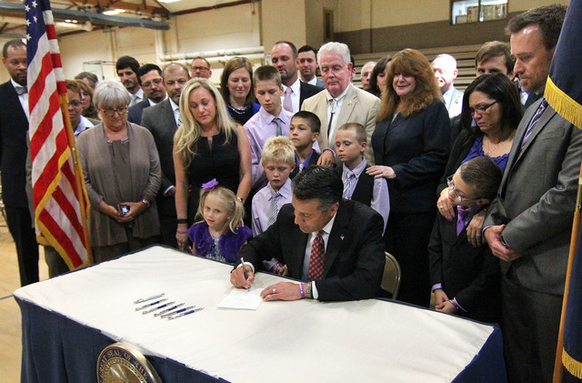 Nevada Gov. Brian Sandoval signs an anti-bullying bill into law at Carson Middle School in Carson City, Nev., on Wednesday, May 20, 2015. Surrounded by lawmakers and the families of students who w ...