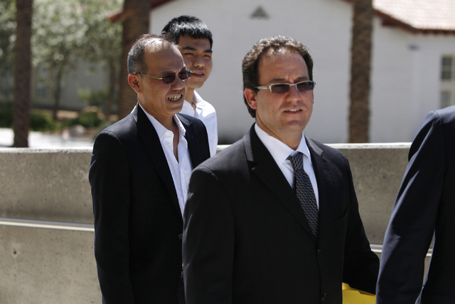 Paul Phua, left, and his son Darren, center, walk to Lloyd George Federal Courthouse in Las Vegas with their attorneys Richard Schonfeld, left, and David Chesnoff, not in the picture, for their ar ...