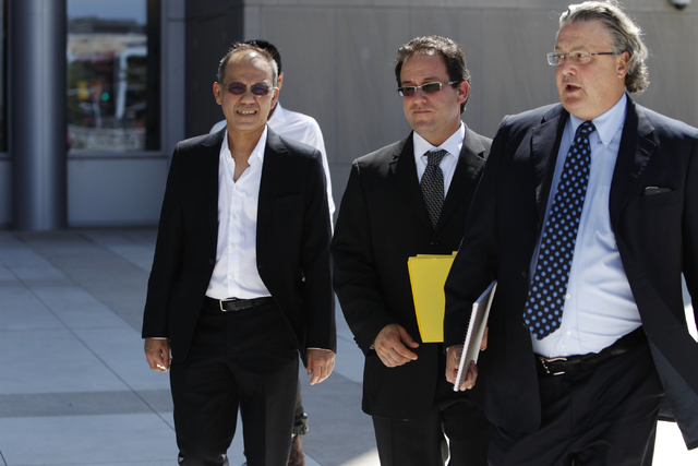 Paul Phua, left, walks to Lloyd George Federal Courthouse in Las Vegas with his attorneys Richard Schonfeld, center, and David Chesnoff for his arraignment Tuesday, Aug. 5, 2014. Phua is accused o ...