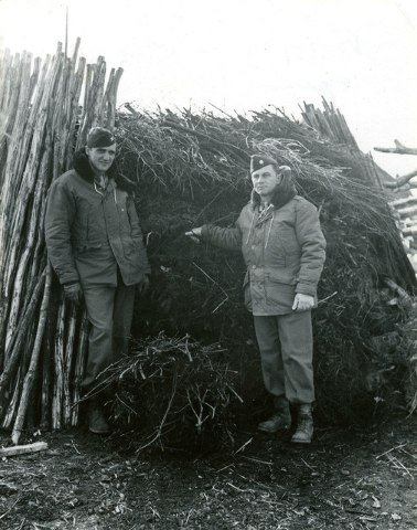 U.S. Army Air Corps officers, Col. Frank Krebs, left, and Maj. Howard Cannon, pose next to a wood pile hidey hole, where the two pilots and Sgt. (no name given) Broga, not shown, hid from German s ...