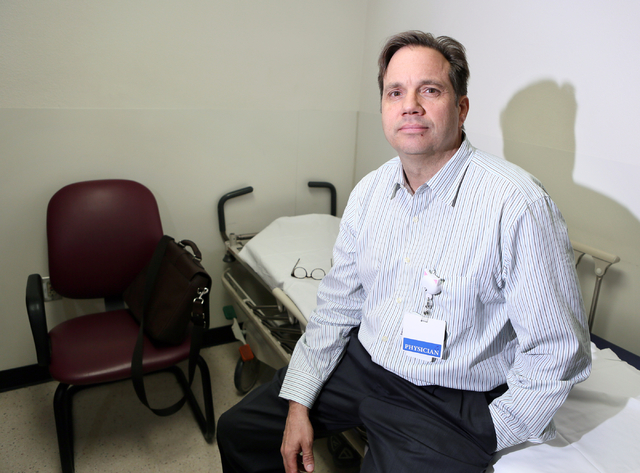 Dr. Jay Fisher, medical director of pediatric emergency services at UMC Children's Hospital of Nevada, sits on a bed in a mental health evaluation room in the emergency room at UMC Children's Hosp ...