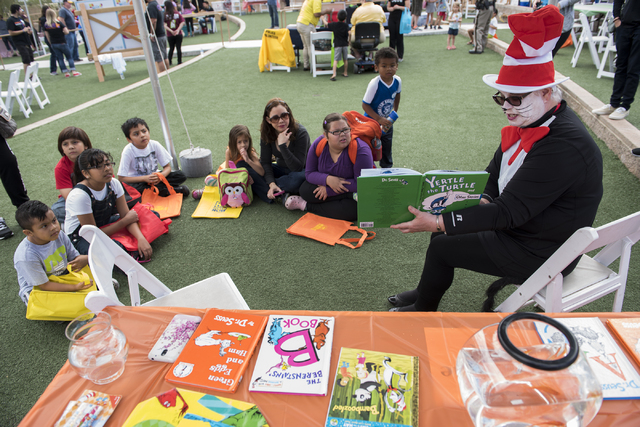 "Volunteer Marilyn Provost dressed in The Cat in the Hat outfit, reads to kids during the ""Flip Through Summer"" program at the Springs Preserve on Saturday, May 16, 2015. The event provides an oppo ..."