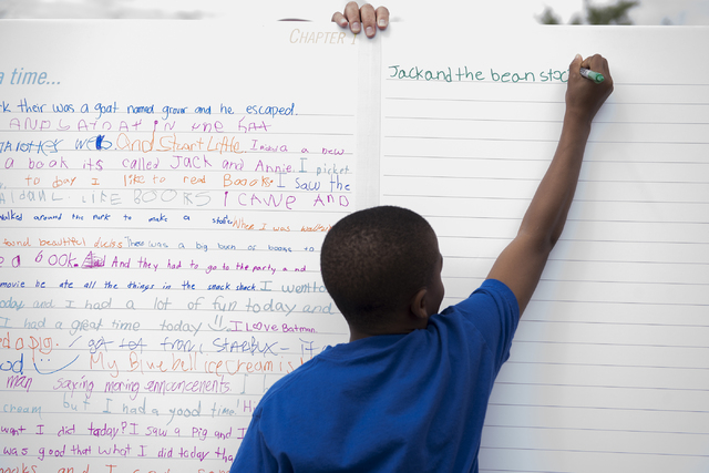 "Emiliyon Daniels, 11, writes down one of his favorite books during the ""Flip Through Summer"" program at the Springs Preserve on Saturday, May 16, 2015. The event provides an opportunity for childr ..."