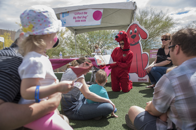 "Volunteer Britt Nwadiashi dressed in Clifford the Big Red Dog outfit, reads to kids during the ""Flip Through Summer"" program at the Springs Preserve on Saturday, May 16, 2015. The event provides a ..."