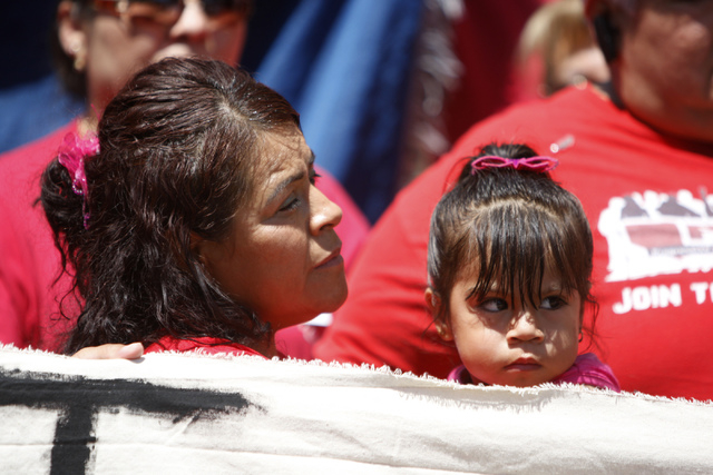 Ivone Meneses holds her daughter Ruby Estrada, 2, during a press conference outside of the Grant Sawyer Building, 555 E Washington Ave., with community activities and allies to demand Attorney Gen ...