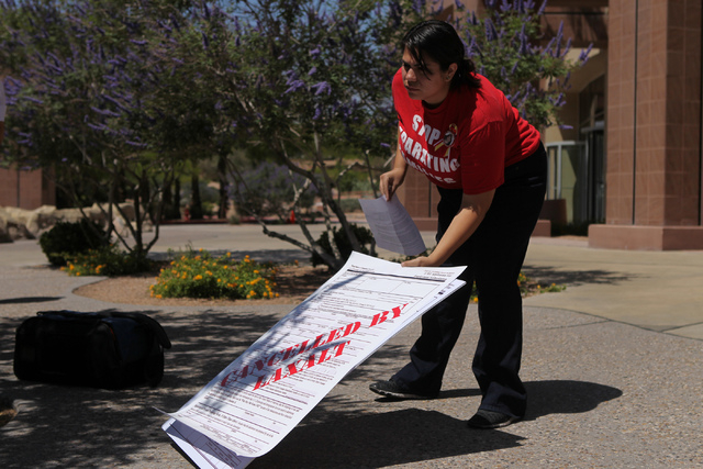 Astrid Silva, organizing director for Progressive Leadership Alliance of Nevada, lowers a sign before a press conference to demand Attorney General Adam Laxalt to remove Nevada from an anti-immigr ...