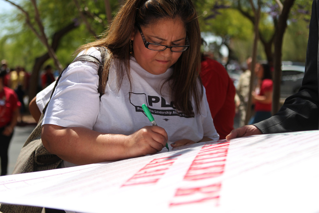 Laura Miranda, who would benefit from President Barack Obama's Deferred Action for Parents of Americans and Lawful Permanent Residents program, signs an employment authorization banner during a pr ...
