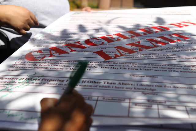 People sign an employment authorization banner during a press conference outside of the Grant Sawyer Building, 555 E Washington Ave., with community activities and allies to demand Attorney Genera ...