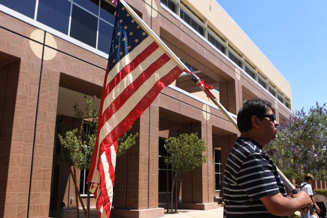 Immigration activist Martin Macias holds an American flag during a press conference outside of the Grant Sawyer Building, 555 E Washington Ave., to demand Attorney General Adam Laxalt to remove Ne ...