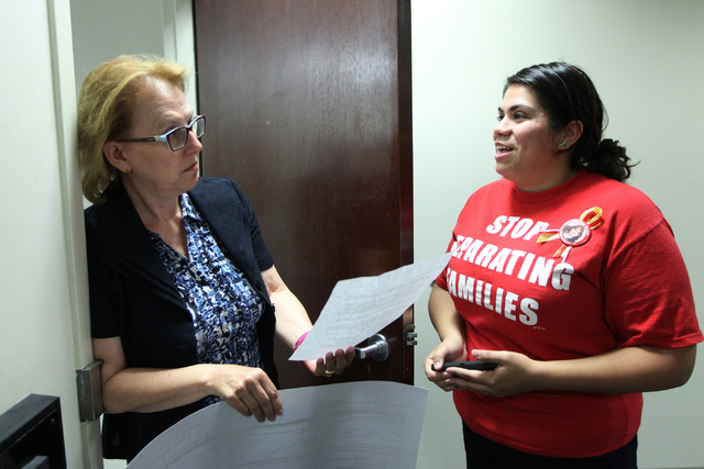 Astrid Silva, right, organizing director for Progressive Leadership Alliance of Nevada, delivers a letter to a representative inside Attorney General Adam Laxalt's office demanding Laxalt to remov ...